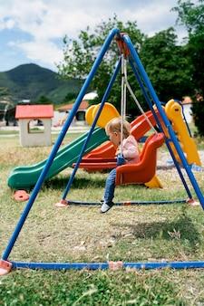 Le petit enfant s'assied sur une vue latérale colorée d'oscillation