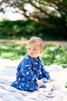 Un petit enfant en salopette bleue est assis sur ses genoux, la tête tournée sur une couverture à carreaux