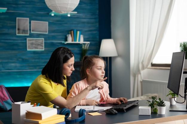 Petit enfant scolarisé à la maison recevant l'aide de sa mère