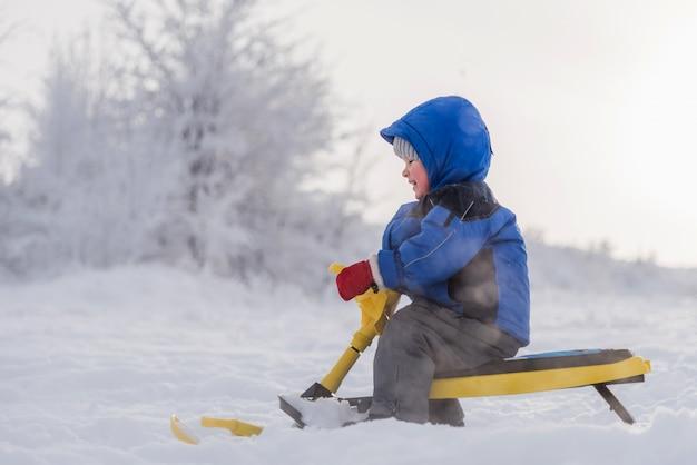 Petit enfant sur un scooter des neiges en hiver