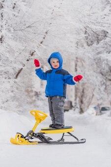 Un petit enfant se dresse sur une scooter des neiges en hiver