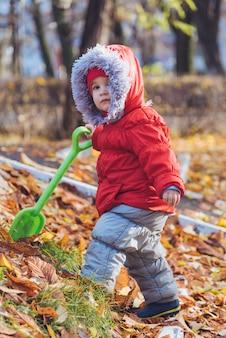 Petit enfant se promène dans le parc avec une pelle