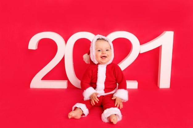 Un petit enfant de six mois dans un costume de père noël est assis près des grands nombres blancs 2021 sur un photophone isolé rouge, espace pour le texte