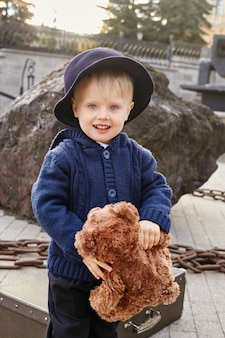 Petit enfant souriant dans le parc, écharpe autour du cou