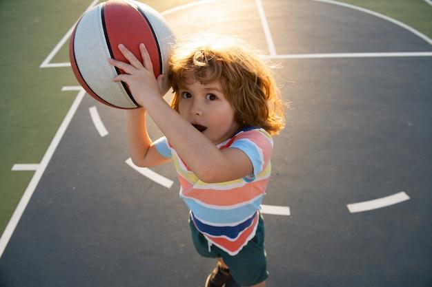 Petit enfant de sport caucasien jouant au basket-ball tenant un ballon avec un visage amusant