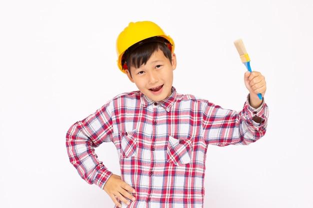 Petit enfant en tant qu'ouvrier du bâtiment portant un casque jaune avec un pinceau à la main