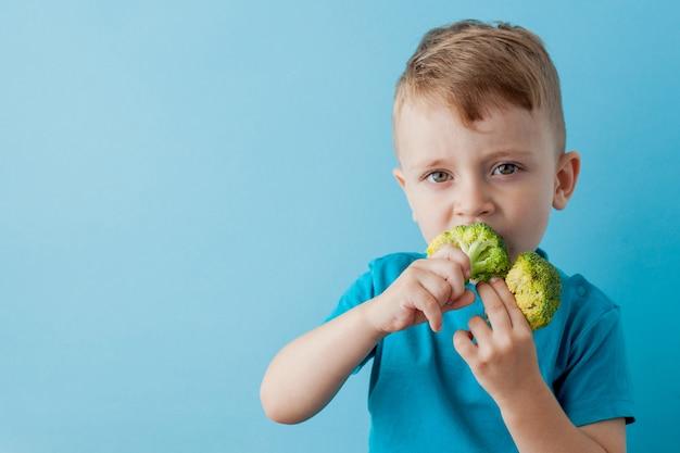 Petit enfant tenant des brocolis dans ses mains sur fond bleu. concept végétalien et sain