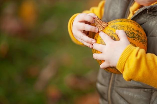 Un petit enfant tenant une citrouille dans ses bras se bouchent.