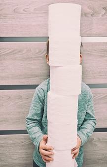 Un petit enfant tenant une grosse pile de papier toilette