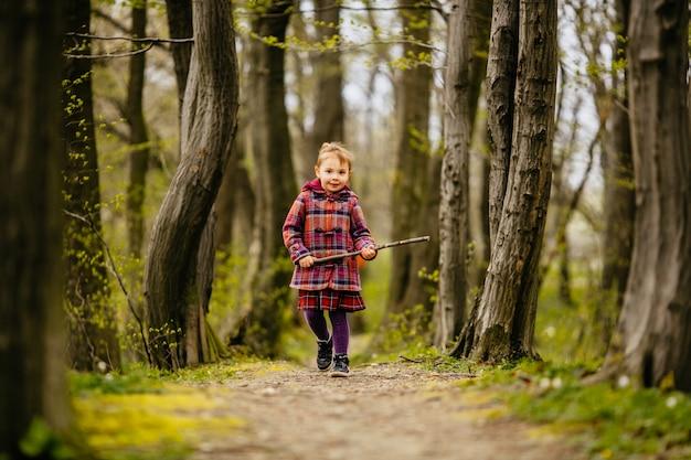 Le petit enfant tenant une malle et marchant le long du parc