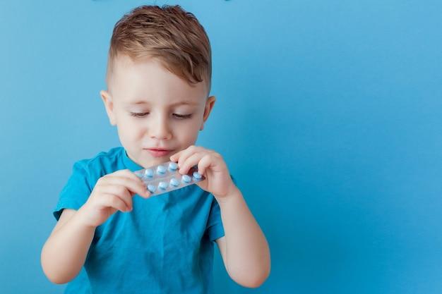 Un petit enfant tient dans sa paume une poignée de pilules sur fond bleu.