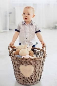 Un petit enfant tient un panier avec des jouets. le concept de l'enfance