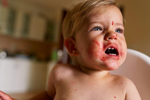 Le petit enfant avec un visage sale fait des grimaces