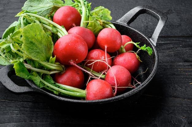 Petit ensemble de radis de jardin, sur table en bois noir