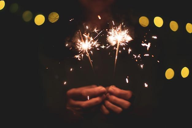 Petit feu d'artifice à la main de cierge magique, célébrant le festival de noël et du nouvel an.