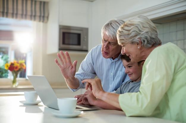 Petit-fils à l'aide d'un ordinateur portable avec des grands-parents