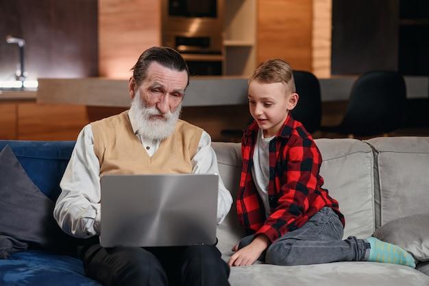 Petit-fils apprend à son grand-père à utiliser un ordinateur portable.