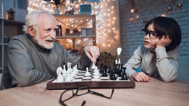 Petit-fils et grand-père jouant aux échecs ensemble