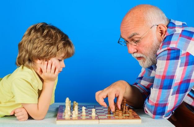 Petit-fils jouant aux échecs avec grand-père. grand-père enseignant aux petits-enfants à jouer aux échecs. relation familiale.
