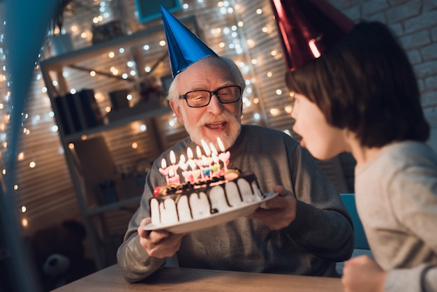 Petit-fils soufflant des bougies sur le gâteau d'anniversaire