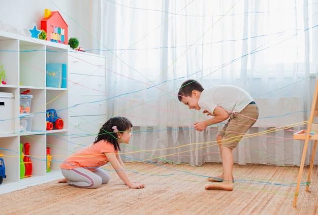 Petit frère de fille, frères et sœurs, friendschild grimpe à travers le web de corde, quête d'obstacles de jeu à l'intérieur.