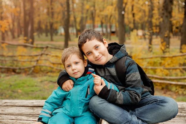 Petit frère avec frère s'asseoir aux relations fraternelles en plein air