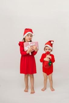 Petit frère et sœur en costumes de noël avec des casquettes avec des cadeaux sur un mur blanc