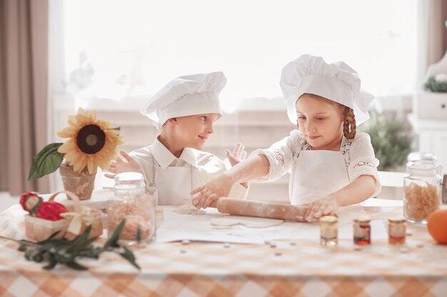Petit frère et sœur préparent le déjeuner dans la cuisine de la maison. le concept d'un passe-temps