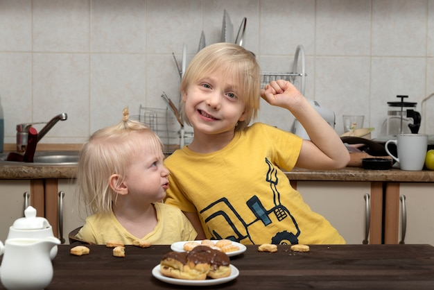 Petit frère et sœur s'amusent dans la cuisine