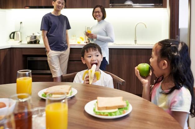 Petit frère et soeur se regardant et mangeant des fruits pour le petit déjeuner dans la cuisine, leurs parents debout en arrière-plan
