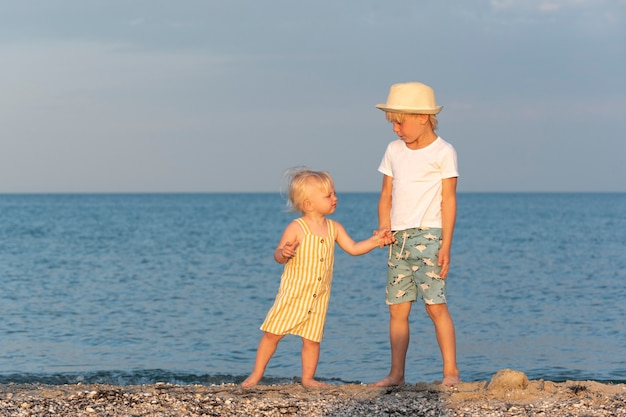 Petit frère et sœur se tiennent la main et marchent le long du bord de mer