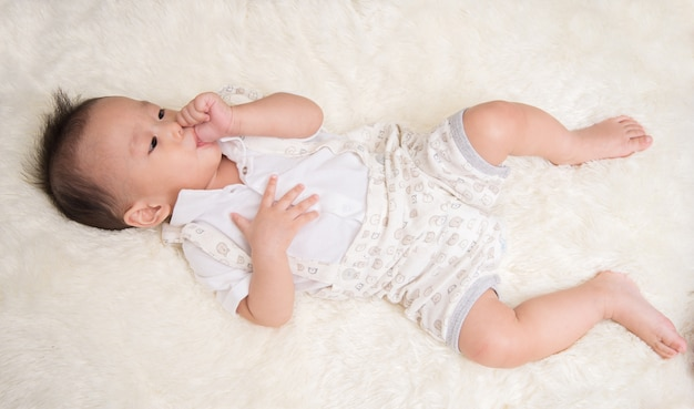 Petit garçon de 7 mois avec le pouce dans la bouche