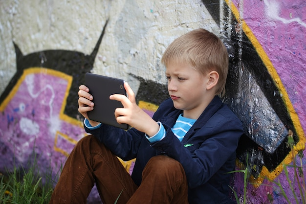 Petit garçon absorbé dans sa tablette pour éduquer et jouer.
