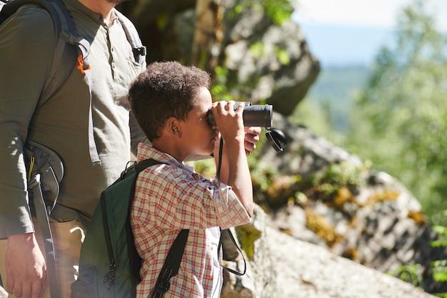 Petit garçon africain regardant à travers les jumelles tout en se tenant dans la nature avec l'homme