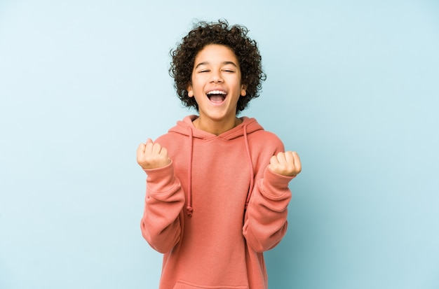 Petit garçon afro-américain isolé acclamant insouciant et excité. concept de victoire.