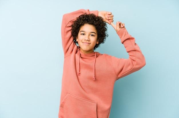 Petit garçon afro-américain isolé étirement des bras, position détendue.