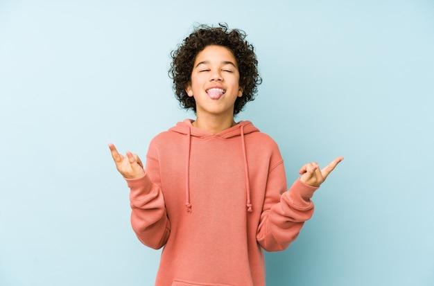 Petit garçon afro-américain isolé montrant le geste de la roche avec les doigts