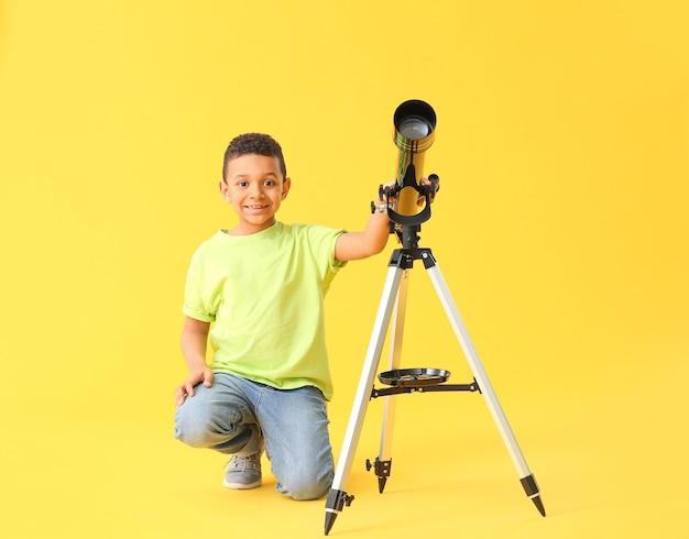 Petit garçon afro-américain avec télescope sur la couleur