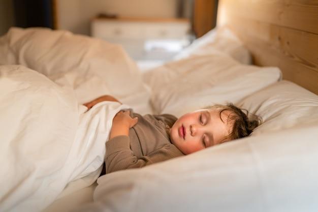 Un petit garçon d'âge préscolaire en pyjama dort dans le lit à la maison le soir. concept de co-dodo.
