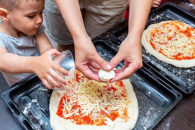 Petit garçon aidant la mère à cuisiner la pizza à la maison