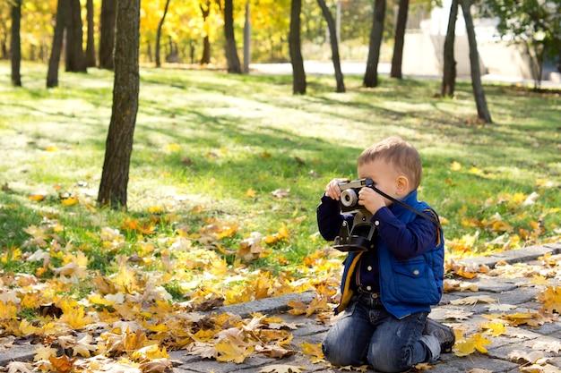 Petit garçon à l'aide d'un appareil photo reflex vintage à genoux sur le sol en regardant à travers le viseur alors qu'il compose sa photo
