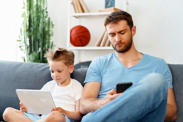 Petit garçon à l'aide de tablette numérique et son père à l'aide de smartphone s'asseoir ensemble sur le canapé à la maison