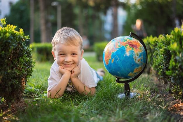 Petit garçon allongé sur l'herbe avec un globe