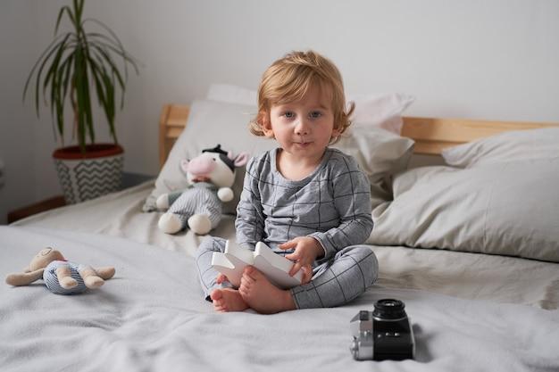 Petit garçon d'un an jouant sur le lit avec ses jouets préférés