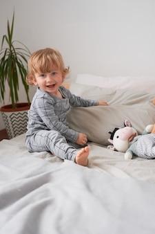 Petit garçon d'un an jouant et s'amusant sur le lit à la maison, photo de style de vie