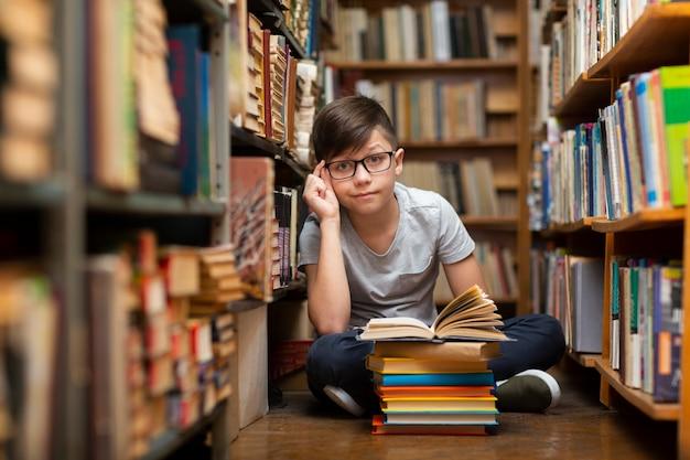 Petit garçon à angle élevé à la bibliothèque