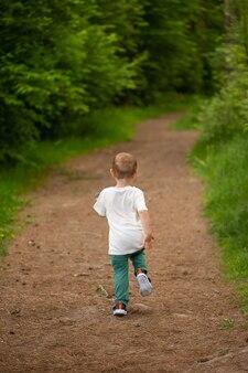 Petit garçon d'années s'enfuit du chemin forestier profondément dans la forêt