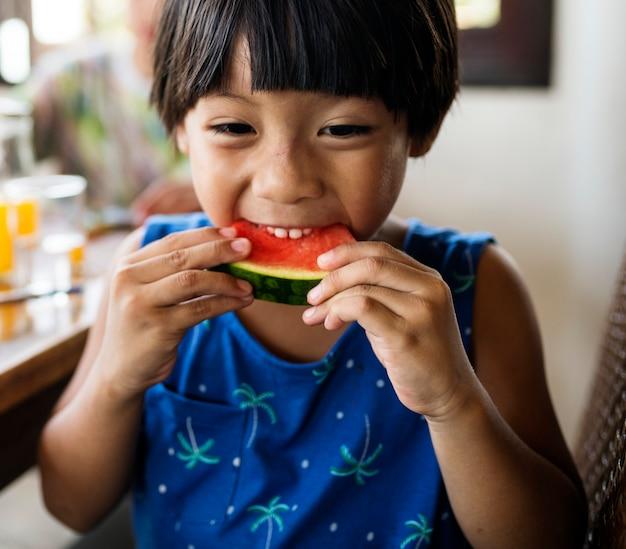 Petit garçon en appréciant un morceau de melon d'eau