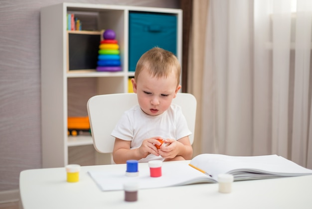 Un petit garçon apprend à dessiner dans un album avec des pinceaux
