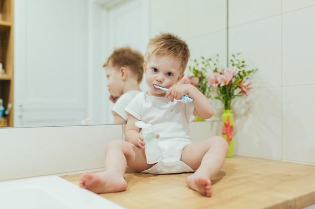 Petit garçon apprend à se brosser les dents dans la salle de bain